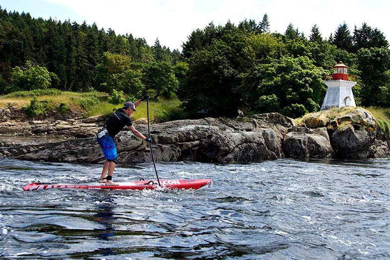 Simon Whitfield paddling by the lighthouse on the way from Vancouver to Victoria