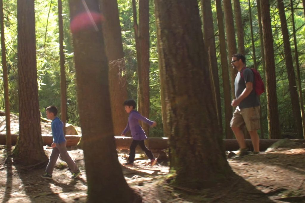 Dean hiking in the woods with his children