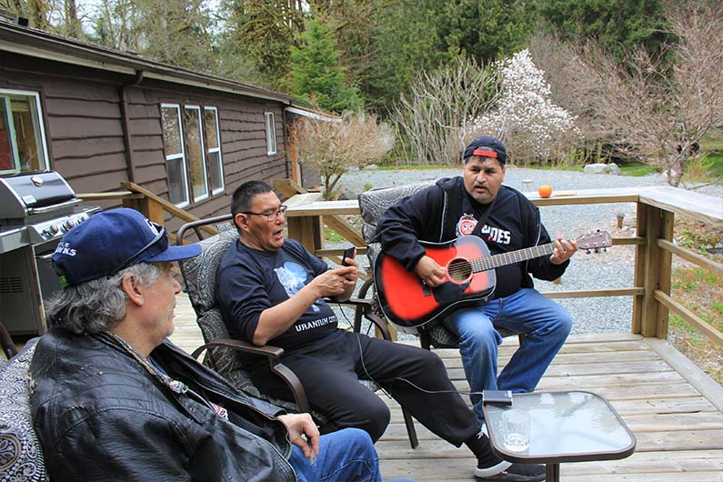 Three indigenous men playing guitar