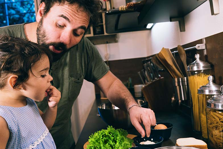 Father and daughter preparing a meal together